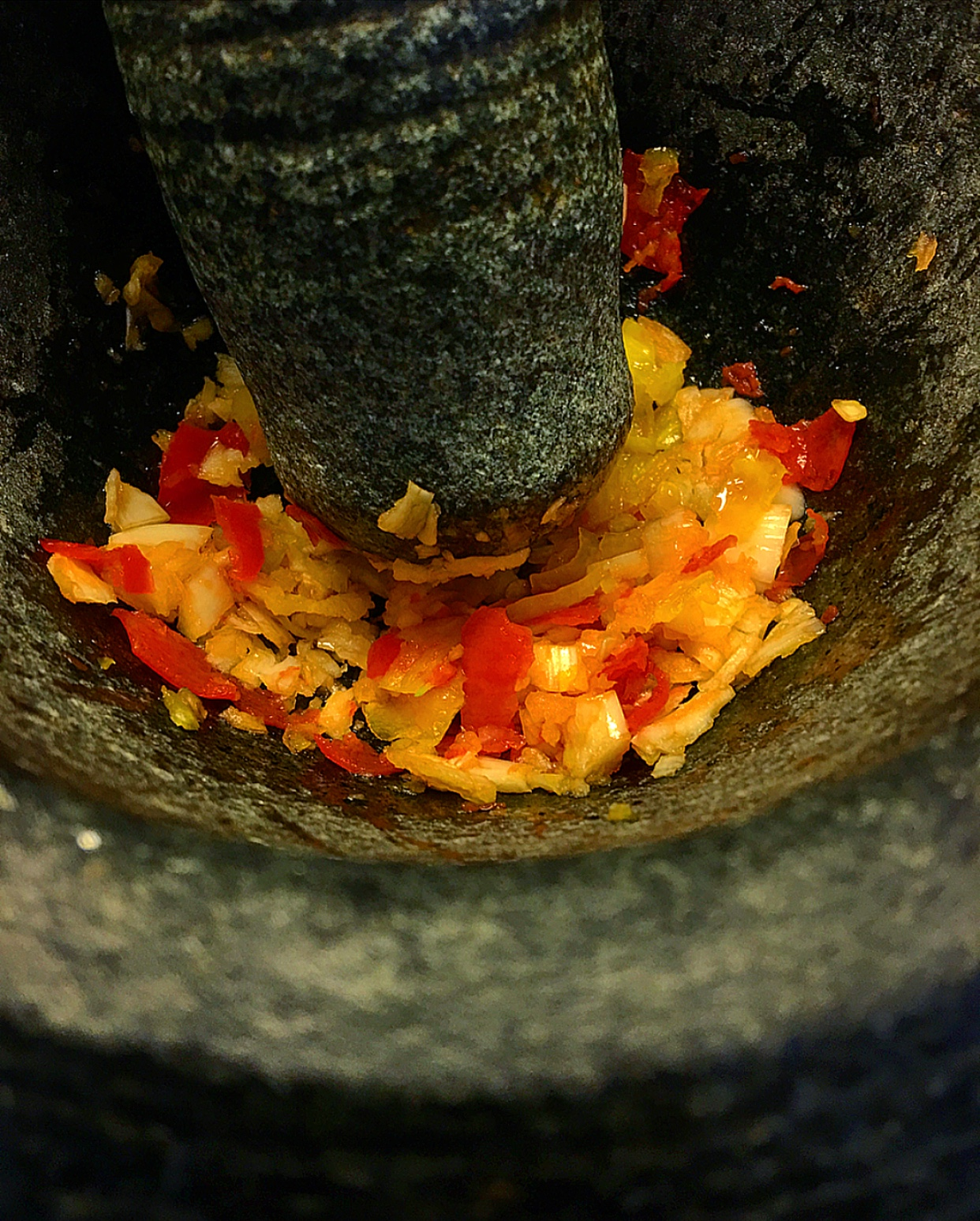 Mash the garlic and peppers in a mortar and pestle.